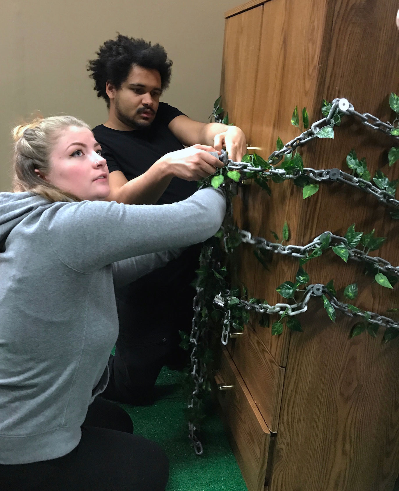 Two students work on cabinet locked with chains